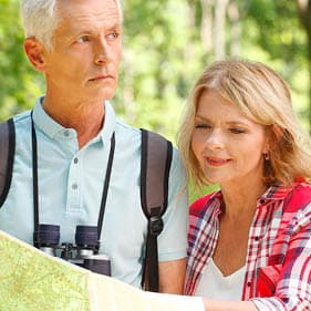 Portrait of senior couple take an excursion. Elderly man with binoculars standing at forest with senior woman and read map while they are hiking.