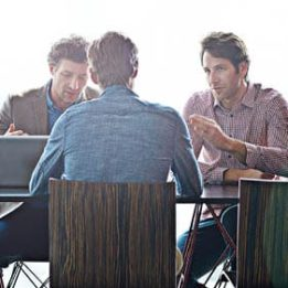 Three businessmen having a discussion around a table.