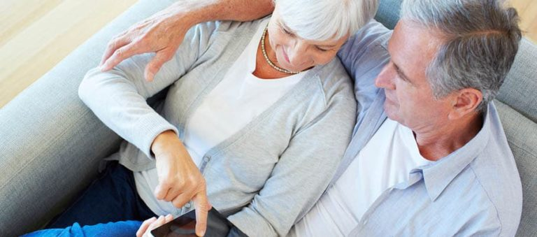 Pensions freedom - High angle shot of a senior couple using a digital tablet while sitting on their sofa