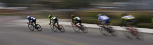 A group of male bicycle racers ride together during a road bike race.