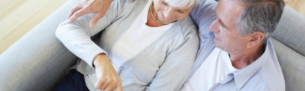 High angle shot of a senior couple using a digital tablet while sitting on their sofa