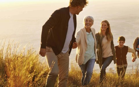 A multi-generational family walking up a grassy hill together at sunset