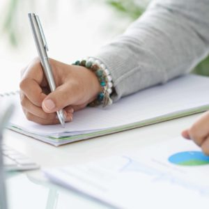 Hands of business person making notes in notepad