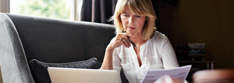Shot of a mature businesswoman going over some paperwork while sitting on her hotel bed