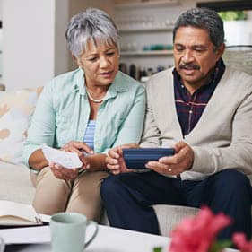 Shot of an elderly couple working out a budget while sitting on the living room sofa