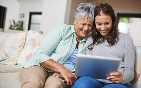 Shot of a young woman showing something to her mother on her tablet while they sit on a sofa together