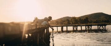Photo of a young woman and her son sailing the toy boat into the lake water while sitting on the dock.// wide photo dimensions